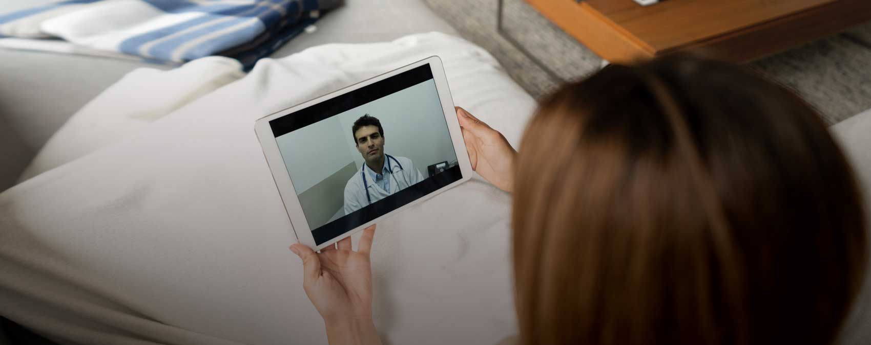 Woman consulting with doctor on tablet